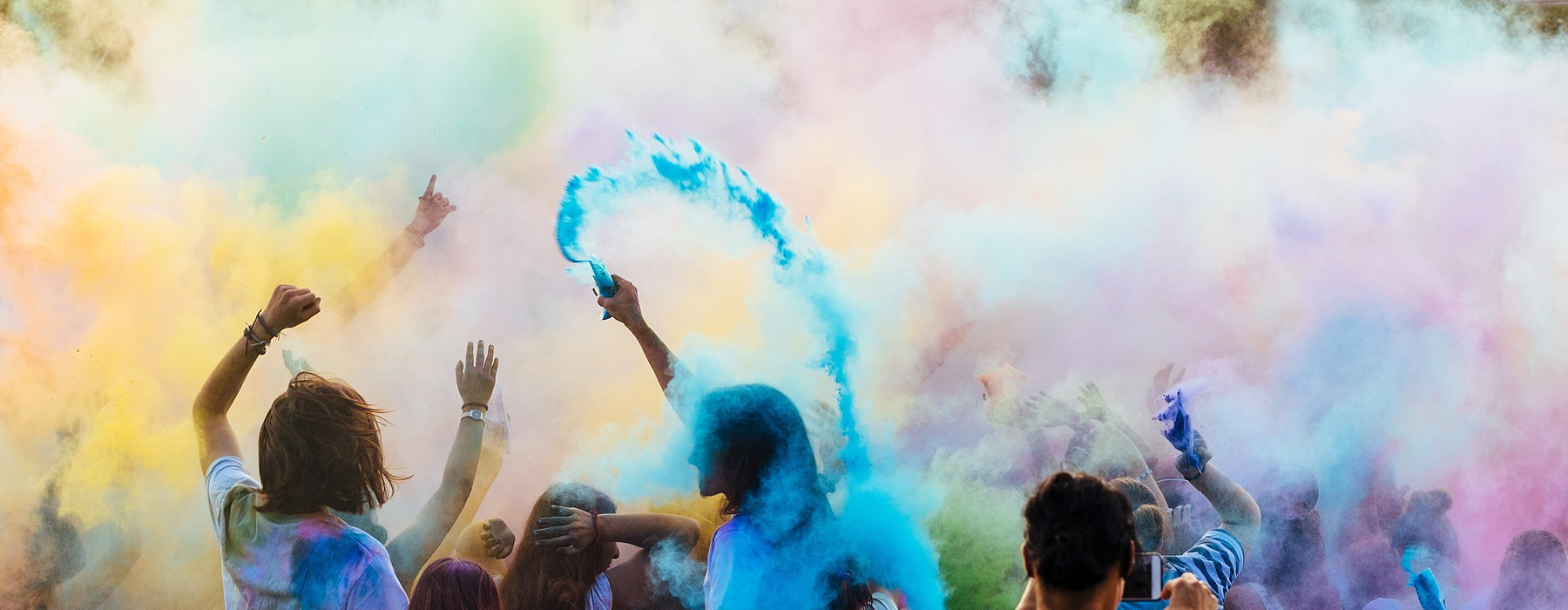 People at an outdoor concert with colored powder